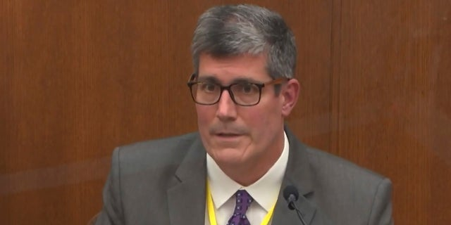 In this image from video, Dr. Andrew Baker, Hennepin County Medical Examiner, testifies as Hennepin County Judge Peter Cahill presides Friday, April 9, 2021, in the trial of former Minneapolis police Officer Derek Chauvin at the Hennepin County Courthouse in Minneapolis, Minn. (Court TV via AP, Pool)