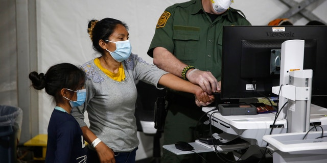 In this March 30, 2021, file photo, a migrant and her daughter have their biometric data entered at the intake area of the U.S. Department of Homeland Security holding facility, the main detention center for unaccompanied children in the Rio Grande Valley, in Donna, Texas. (AP Photo/Dario Lopez-Mills, Pool, File)