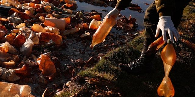 یک افسر پلیس چهارشنبه ، 7 آوریل 2021 بطری های پلاستیکی دور ریخته شده از رودخانه آلوده Tagaret را که به دریاچه اورو اورو ، نزدیک اورورو ، بولیوی می ریزد ، خارج کرد. عملیات پاکسازی از چهارشنبه برای بازگرداندن زیبایی های طبیعی دریاچه آغاز شد.  پر از زباله های پلاستیکی و سایر زباله های مصنوعی.  (عکس AP / خوان کاریتا)