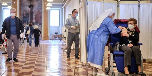Un operatore sanitario somministra il vaccino Pfizer a una donna dell'Ospedale San Giovanni Adolorata di Roma sabato 10 aprile 2021.  (Associated Press)