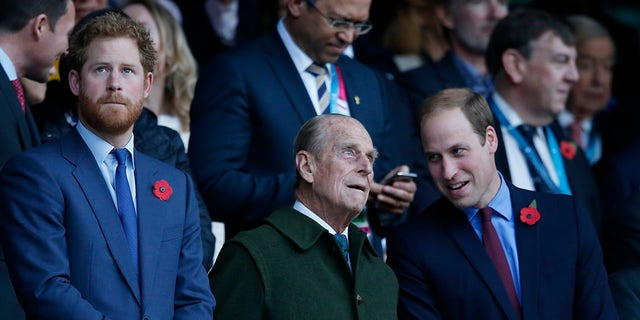 Prince Harry (L) and his brother Prince William (R) stand with their grandfather the Duke of Edinburgh (C) as they wait for the start of the Rugby World Cup final between New Zealand and Australia at Twickenham Stadium.