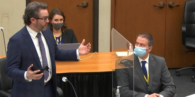 In this image from video, defense attorney Eric Nelson, left, discusses motions before the court as defendant, former Minneapolis police officer Derek Chauvin, right, and Nelson's assistant Amy Voss, back, listen, Monday, April 12, 2021, as Hennepin County Judge Peter Cahill presides over the trial of Chauvin at the Hennepin County Courthouse in Minneapolis. (Court TV, via AP, Pool)