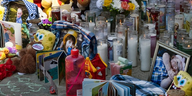 Photos, candles, flowers and balloons are placed as a memorial for three children who were killed at the Royal Villa apartments complex in the Reseda section of Los Angeles. Authorities have identified 3-year-old Joanna Denton Carrillo, her 2-year-old brother, Terry, and 6-month-old sister, Sierra. (AP Photo/Richard Vogel)