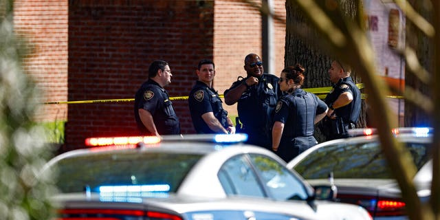 Knoxville police work the scene following a shooting at Austin-East Magnet High School in Knoxville, Tenn., Monday, April 12, 2021. (AP Photo/Wade Payne)