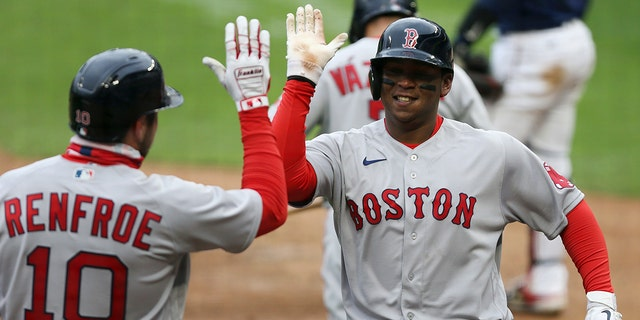 Boston Red Sox Rafael Devers (11) high fives teammate Boston Red Sox Hunter Renfroe (10) after hitting a home run against the Minnesota Twins during the ninth inning of a baseball game, Tuesday, April 13, 2021, in Minneapolis. Boston won 4-2.