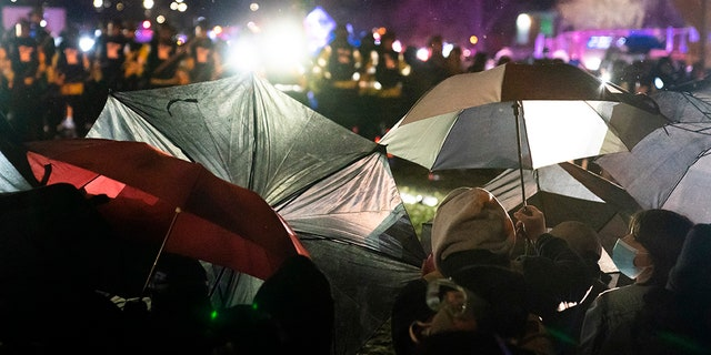 Demonstrators use umbrellas as shields against police during a clash outside the Brooklyn Center Police Department while protesting the shooting death of Daunte Wright, late Tuesday, April 13, 2021, in Brooklyn Center, Minn. (AP Photo/John Minchillo)