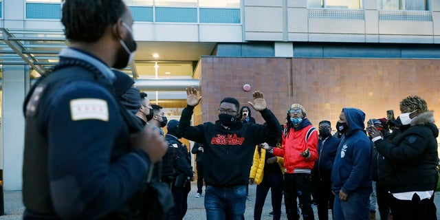 Activist Ja'Mal Green reacts as he walks towards a line of police officers outside Chicago police headquarters during a rally after the body camera video release of fatal police shooting of 13-year-old Adam Toledo on Thursday, April 15, 2021. (AP Photo/Shafkat Anowar)