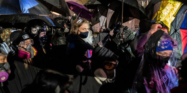 Demonstrators using umbrellas as shields against potential crowd control weapons take part in a protest in response to the fatal shooting of Daunte Wright during a traffic stop, outside the Brooklyn Center (Minn.) Police Department on Thursday, April 15, 2021. (Associated Press)