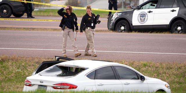 Two Bureau of Criminal Apprehension agents begin investigating the scene of an officer-involved shooting, Sunday, April 18, 2021, in Burnsville, Minn.