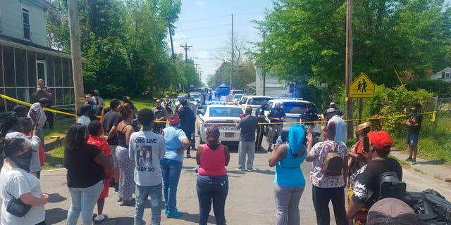 Residents gather near the scene of a shooting, Wednesday, April 21, 2021 in Elizabeth City, N.C. At least one law enforcement officer with a sheriff's department in North Carolina shot and killed a man while executing a search warrant Wednesday, the sheriff's office said. (Chris Day/The Daily Advance via AP)