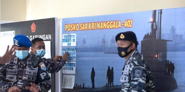 Een Indonesische militaire functionaris plaatst foto's van leden van de Indonesische marine op een KRI Nanggala-onderzeeër die vermist werd tijdens deelname aan een training woensdag, op Ngurah Rai Airport, Bali, Indonesië, op vrijdag 23 april 2021 (AP Photo / Firdia Lisnawati)