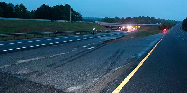 This photo provided by the Gwinnett County Police Department shows tire marks on the pavement, front, near the scene of a deadly crash in Gwinnett County, Ga., Saturday, April 24. 2021. Police in Georgia say multiple people died and several others were hurt in the interstate crash. Gwinnett County police say the crash left a passenger van engulfed in flames and rolled on its side Saturday evening. (Gwinnett County Police Department via AP)