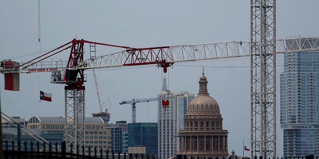 Construction cranes hover over downtown and near the State Capitol, Monday, April 26, 2021, in Austin, Texas. Texas' torrid growth over the past decade is paying off with a major boost in political clout. (AP Photo/Eric Gay)
