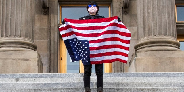 A student holding a U.S. Flag upside down stands atop the steps at the Idaho Capitol Building Monday, April 26, 2021 in Downtown Boise. (Darin Oswald /Idaho Statesman via AP)