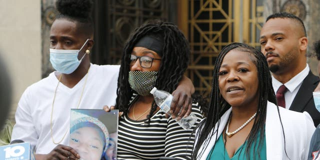 Myron Hammonds, left, and Paula Bryant, center, father and mother of Ma'Khia Bryant, the 16-year-old girl shot and killed by a Columbus police officer on April 20, stand next to family attorney Michelle Martin during a news conference Wednesday in Columbus, Ohio. (AP Photo/Jay LaPrete)