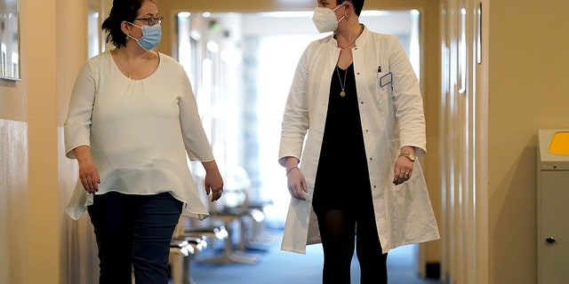 April 14, 2021: Joerdis Frommhold, right, head doctor of the 'MEDIAN Clinic Heiligendamm', speaks with patient Simone Ravera, left, after an interview with the Associated Press.