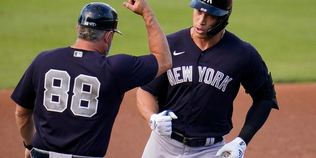 New York Yankees' Aaron Judge, right, rounds third to greetings from coach Phil Nevin after hitting a two-run home run off Philadelphia Phillies starting pitcher Matt Moore during the first inning of a spring training baseball game in Clearwater, Fla., Thursday, March 25, 2021. (AP Photo/Gene J. Puskar)