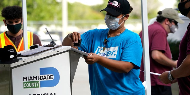 FILE - In this Oct. 26, 2020 file photo, an election worker stamps a vote-by-mail ballot dropped off by a voter before placing it in an official ballot drop box before at the Miami-Dade County Board of Elections in Doral, Fla. (AP Photo/Lynne Sladky, File)