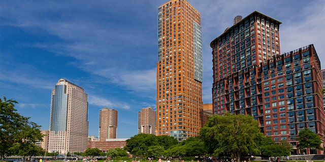 Battery Park City with Citygroup building (on the left) in background, Lower Manhattan, New York City. People are relaxing and enjoying a beautiful summer day outside. Wide angle lens.