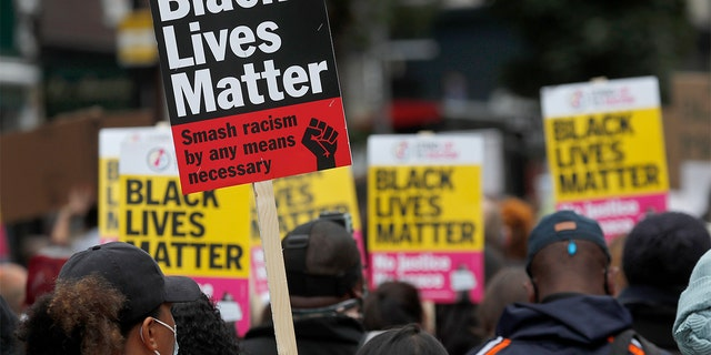 "FILE - In this file photo dated Sunday, Aug. 30, 2020, Black Lives Matter protesters hold posters as they march through Notting Hill during the ""Million People March"" through central London. (AP Photo/Frank Augstein, FILE)"