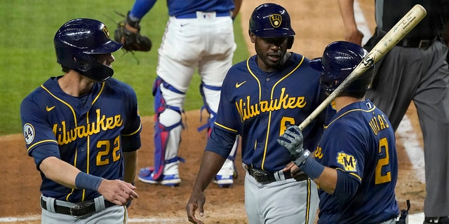 Milwaukee Brewers' Christian Yelich (22), Lorenzo Cain (6) and Luis Urias (2) celebrate after Yelich and Cain scored on an Orlando Arcia double in the sixth inning of a preseason baseball game against the Texas Rangers in Arlington, Texas, Monday, March 29, 2021. (AP Photo/Tony Gutierrez)