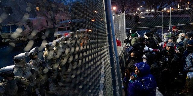 Authorities guard a perimeter fence as demonstrators gather on the other side Tuesday outside the Brooklyn Center Police Department. (AP)