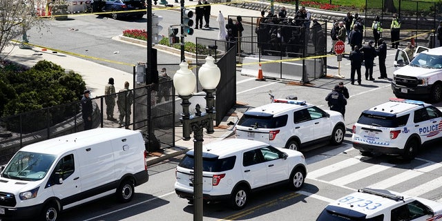 Police officers gather near a car that crashed into a barrier Friday on Capitol Hill in Washington. One Capitol Police officer and a suspect have died. (AP Photo/J. Scott Applewhite)