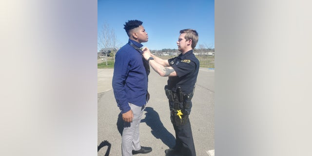 Officer Adam Price helps 18-year-old Jalen Lewis tie a tie.