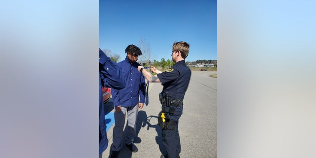 Officer Adam Price helps 18-year-old Elijah Darling tie a tie.