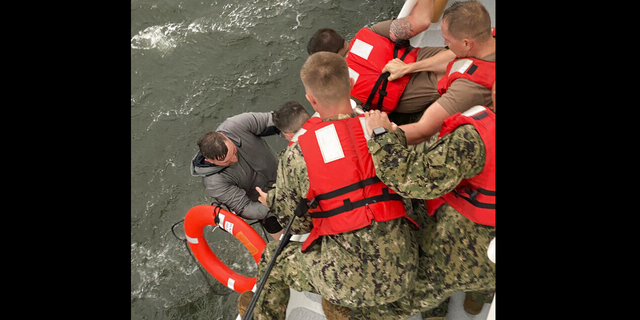 Coast Guard members pull a person from the water Tuesday after the Seacor Power capsized. (AP/US Coast Guard)