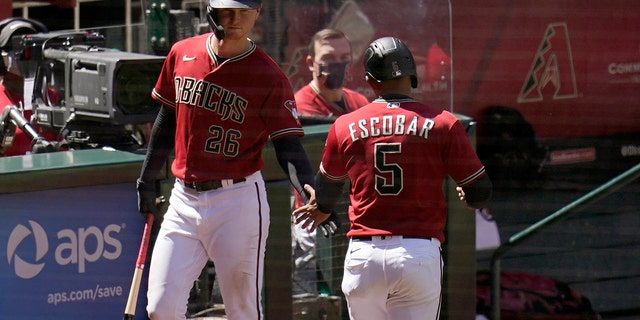 Arizona Diamondbacks' Eduardo Escobar (5) celebrates his run scored against the Cleveland Indians with Diamondbacks' Pavin Smith (26) during the fourth inning of a spring training baseball game Tuesday, March 30, 2021, in Phoenix. (AP Photo/Ross D. Franklin)