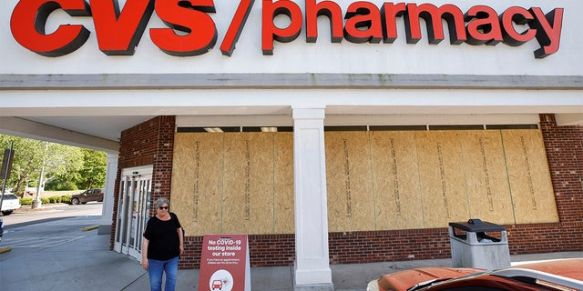 A shopper leaves a store with windows boarded up in anticipation of possible looting or vandalism following the killing of Andrew Brown Jr. by sheriffs last week, in Elizabeth City, North Carolina, U.S. April 27, 2021.