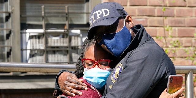 A police officer embraces a community leader in front of the building where a man shot his child's mother and two of her daughters dead before turning his gun on himself, Tuesday, April 6, 2021 (AP Photo / Mary Altaffer)