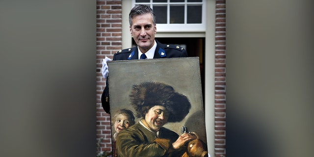 "This photograph taken on November 3, 2011, shows District Chief of Alblasserwaard, Bart Willemsen showing the recovered painting ""Two Laughing Boys"" by Frans Hals which was stolen from the Leerdam Museum in May 2011. (Photo by ILVY NJIOKIKTJIEN/ANP/AFP via Getty Images)"