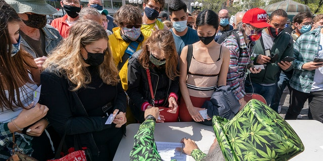 "A man wearing a cannabis costume hands out marijuana cigarettes in New York during a ""Joints for Jabs"" event, where adults who showed their COVID-19 vaccination cards received a free joint. (AP Photo/Mark Lennihan, File)"