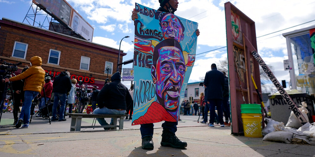 A man holds a sign at George Floyd Square, Wednesday, April 21, 2021, in Minneapolis, a day after former Minneapolis police Officer Derek Chauvin was convicted on all counts for the 2020 death of Floyd.