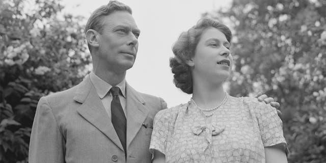 La princesa Isabel con su padre, el rey Jorge VI, en los jardines del Castillo de Windsor, Inglaterra, el 8 de julio de 1946.
