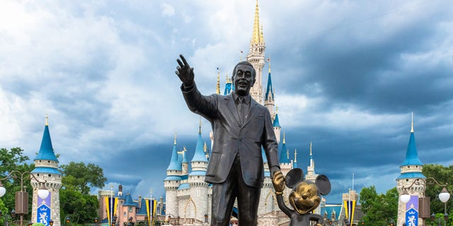 Disney World guests gather near the Walt Disney and Mickey Mouse statue inside of the Magic Kingdom theme park in this July 2019 photo. (Roberto Machado Noa/LightRocket via Getty Images)