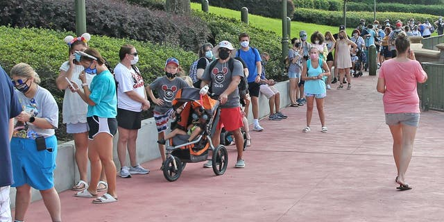 Guests in protective masks wait to pick up their tickets at the Magic Kingdom theme park at Walt Disney World on the Florida theme park's reopening day, July 11, 2020. (GREGG NEWTON/Gregg Newton/AFP via Getty Images)