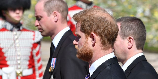Prince William, Duke of Cambridge; Prince Harry, Duke of Sussex and Peter Phillips walk behind Prince Philip, Duke of Edinburgh's coffin, carried by a Landrover hearse, in a procession during the funeral of Prince Philip, Duke of Edinburgh at Windsor Castle on April 17, 2021, in Windsor, United Kingdom.
