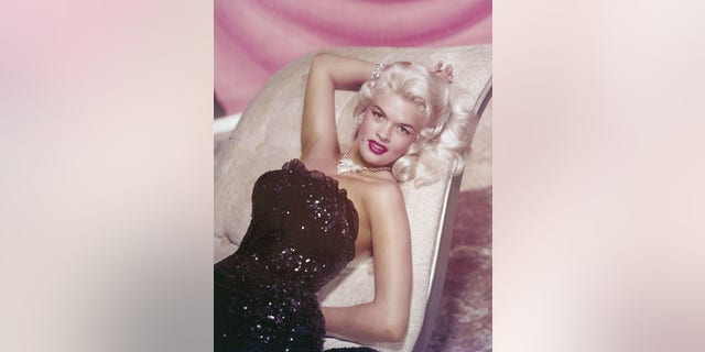 Studio portrait of American actor Jayne Mansfield reclining on chaise longue in a strapless sequined gown and diamond jewelry, circa 1955.