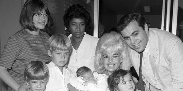 Actress Jayne Mansfield and family are pictured here as the blonde actress leaves Cedars of Lebanon Hospital with the newest addition to the family, baby Anthony. Left to right are Jayne Marie Mansfield, 15, Zoltan Hargitay, 5, Mickey Hargitay Jr., 6, unidentified hospital attendant, Jayne holding baby Anthony, and husband Matt Cimber with Mariska Hargitay, 1. Anthony is the first child by Cimber.