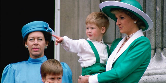 Diana, Princess Of Wales, holding Prince Harry as she watched Trooping the Colour with Prince William and Princess Margaret from the balcony of Buckingham Palace.