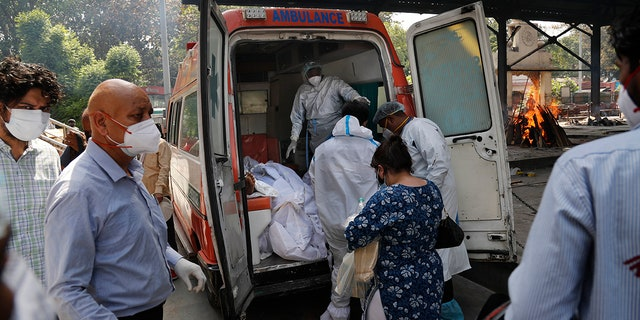 April 19, 2021: Health workers prepare to take out bodies of six victims of COVID-19 from an ambulance for cremation in New Delhi, India.