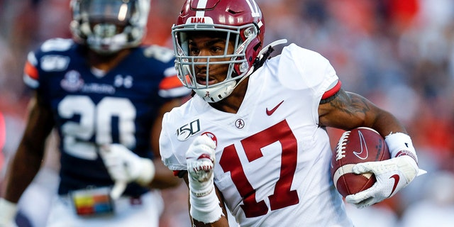 FILE - In this Saturday, Nov. 30, 2019 file photo, Alabama wide receiver Jaylen Waddle (17) carries the ball in for a touchdown after a reception in the first half of an NCAA college football game against Auburn in Auburn, Ala. (AP Photo/Butch Dill, File)