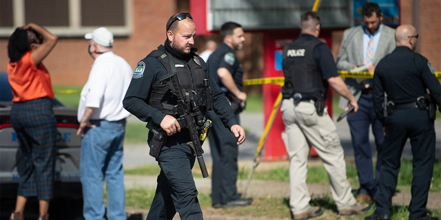 Police work in the area of Austin-East Magnet High School after a reported shooting Monday, April 12, 2021. Authorities say multiple people including a police officer have been shot at the school. (Saul Young/The News Sentinel via AP)