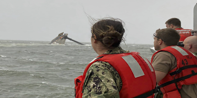 Coast Guard members scan the water Tuesday while searching for those missing after the Seacor Power, a 129-foot-ship, overturned near Louisiana. (AP/U.S. Coast Guard)