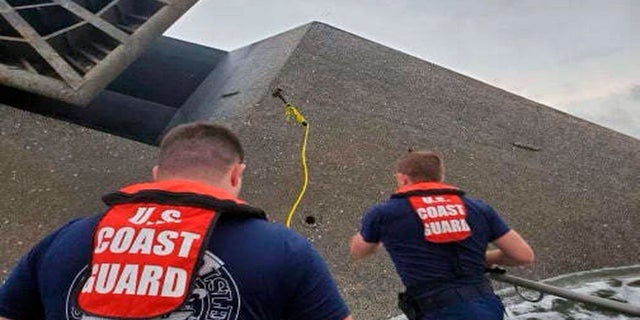 Coast Guard Station Grand Isle 45-foot Response Boat-medium boat crew members attempt to throw a hammer Thursday at the hull of the SeaCor Power. The crew was attempting to make contact with potential survivors inside the vessel. (AP/U.S. Coast Guard)