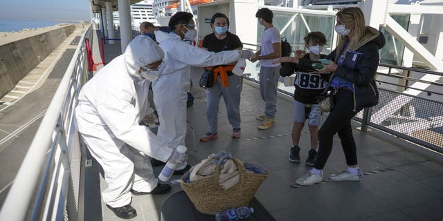 Passengers have their hand luggage sanitized prior to boarding the MSC Grandiosa cruise ship in Civitavecchia, near Rome, Wednesday, March 31, 2021. (AP Photo/Andrew Medichini)