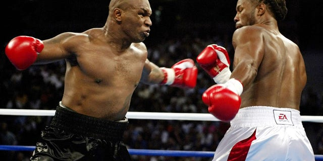 Mike Tyson (L) and Lennox Lewis trade punches during round one of their WBC/IBF/IBO World Heavyweight Championship bout at the Pyramid Arena in Memphis, Tennessee, June 8, 2002.